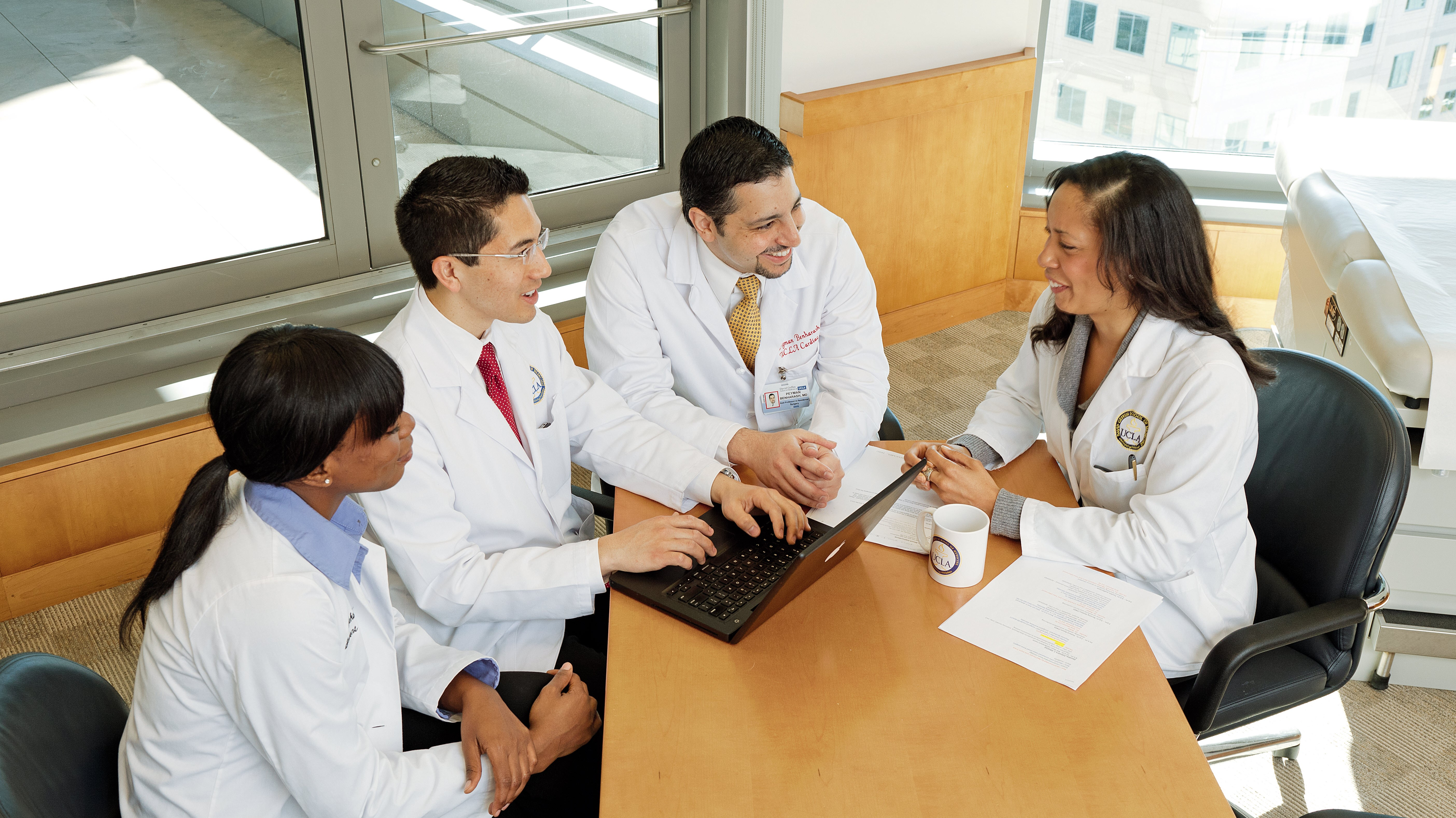 Four clinicians sitting around laptop