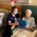 Image of UCLA Health nurse helping a patient use the bedside devices.